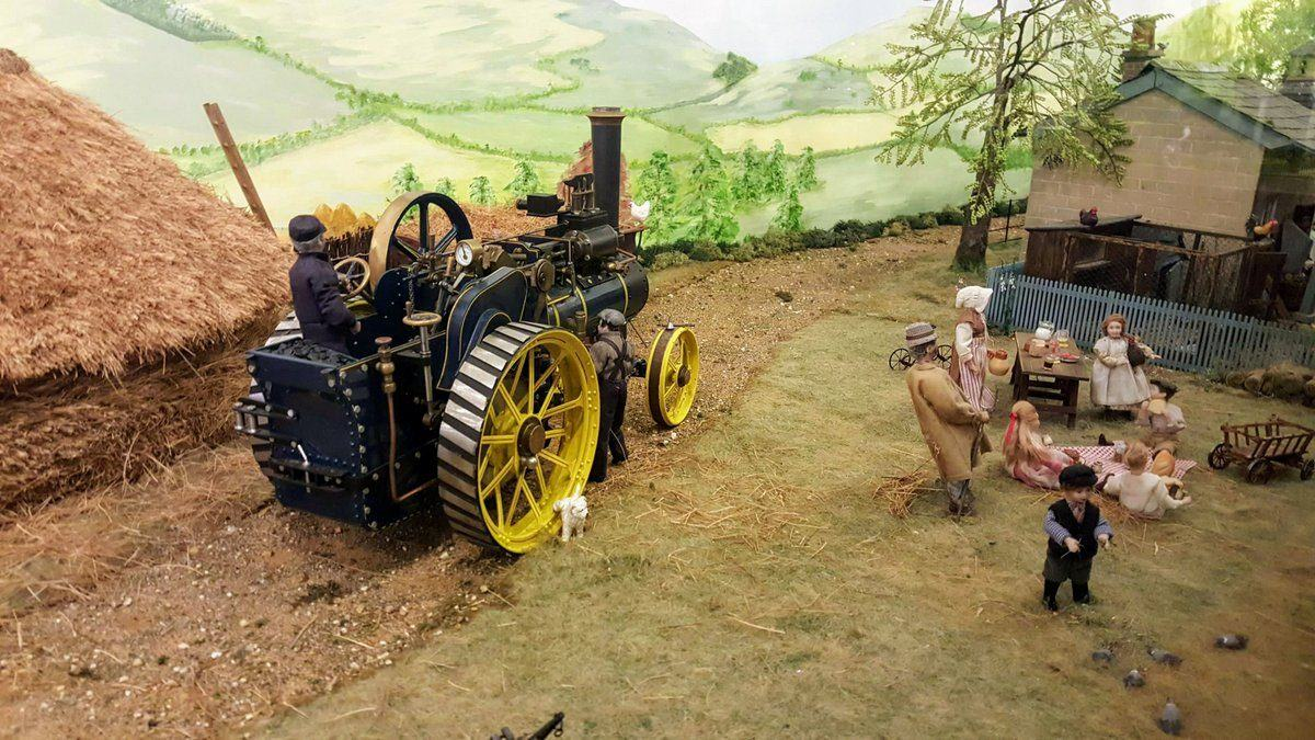 Model diorama rural scene with two labourers attending a steam traction engine and a family playing nearby
