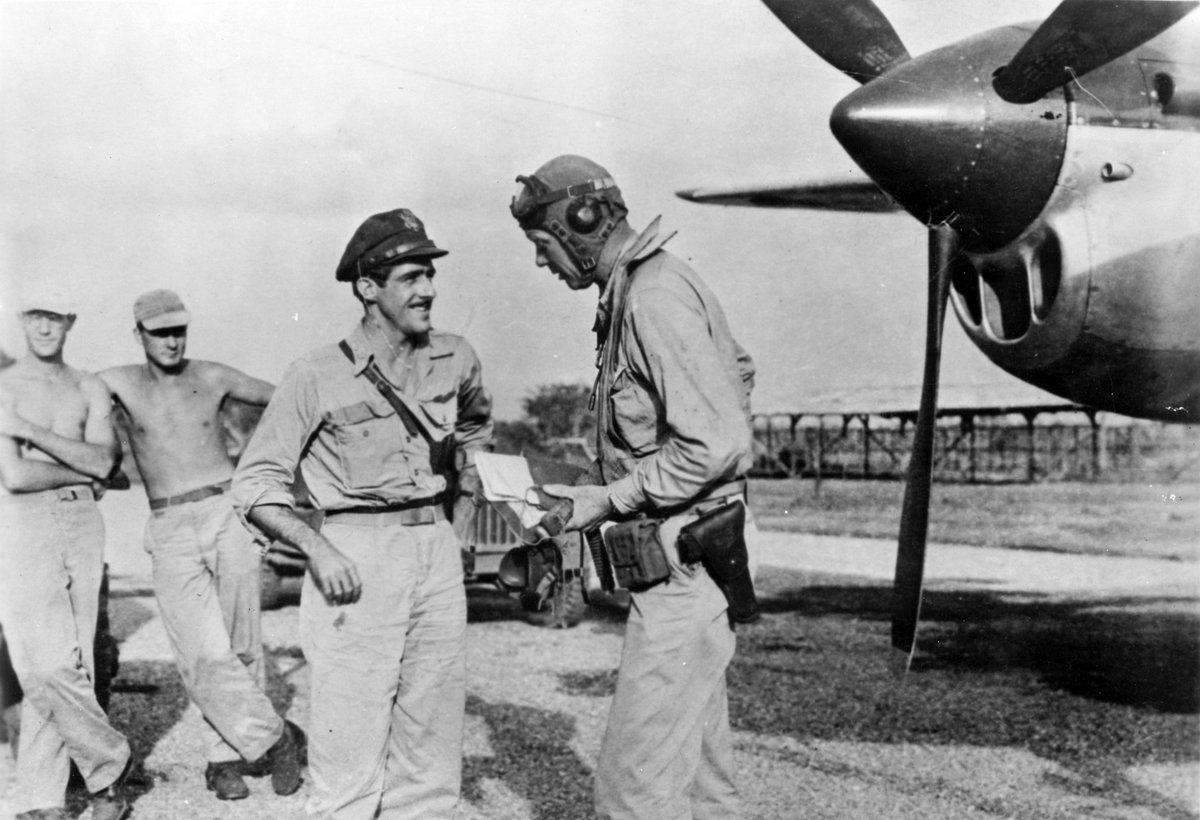 Charles A. Lindbergh talking with Maj. Thomas B. McGuire in front of a P38 with ground crew in the background.