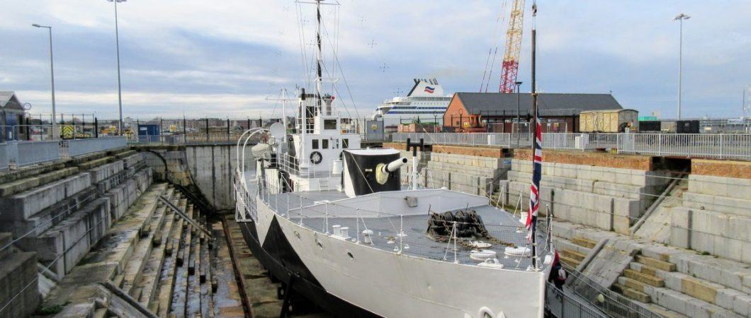 Looking down on a grey and black camouflaged gunboat in a dry dock
