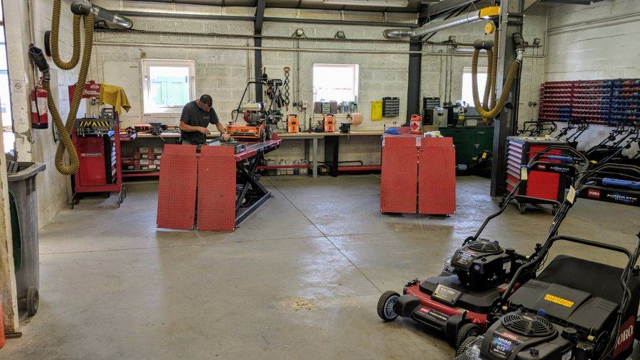 A mechanic works on a motor lawnmower on his workshop bench