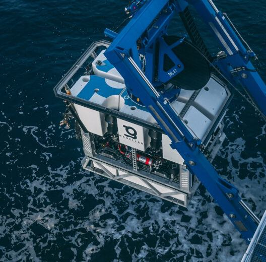 A box shaped ROV being lowered into the sea