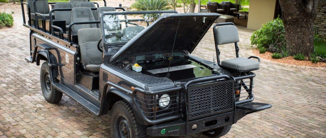 A green Landrover safari viewing vehicle with its bonnet open displaying the battery pack