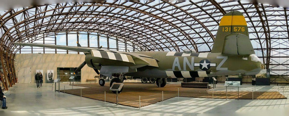 A green camouflaged twin-engined bomber in a glass hanger