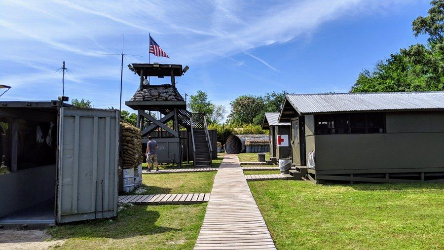 Vietnam War erea huts and duckboards on green grass. A wooden observation tower with an American flag dominates