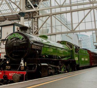 Classic steam locomotive in glistening green livery alongside the platform