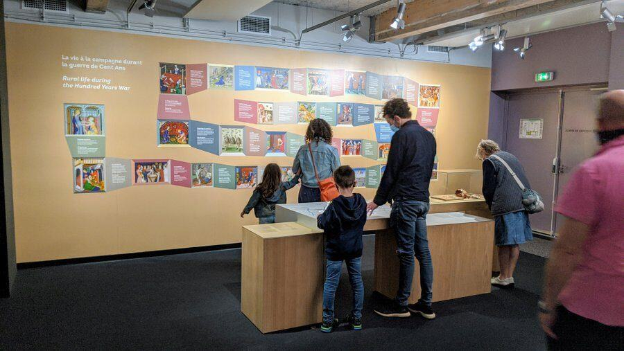A family study a wall display of medieval images at Centre 1415 Azincourt