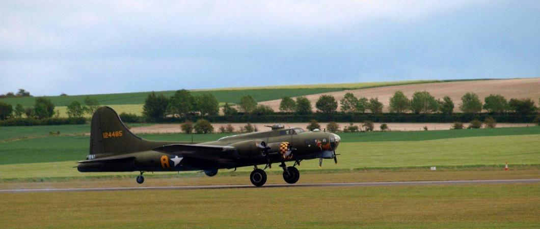 A green B-17 four engine bomber just lifts off the runway with fields, trees and a blue sky in the background
