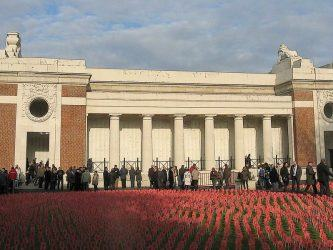People queue to enter the classic mausoleum-like building with a field of red poppies in the foreground