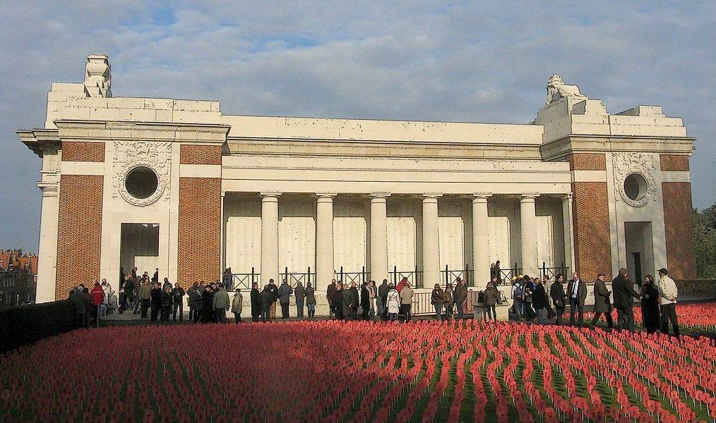 People queue to enter the classic mauseleum-like building with a field of rep poppies in the foreground