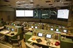 A view across the Mission Control Room with rows of consoles facing the wall screens