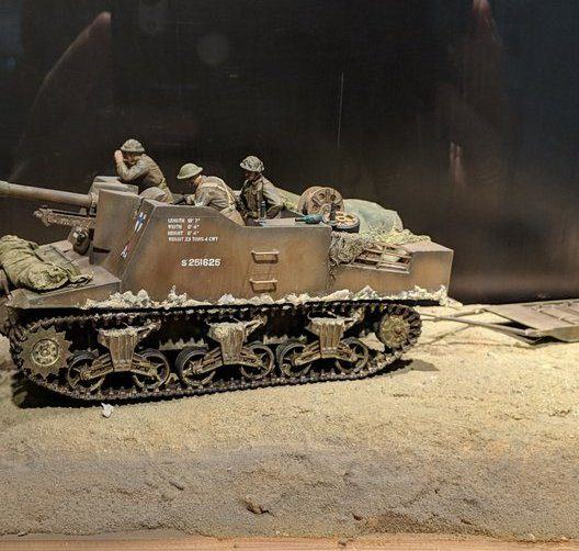 A model of a tracked artillery gun with crew on a sandy beach