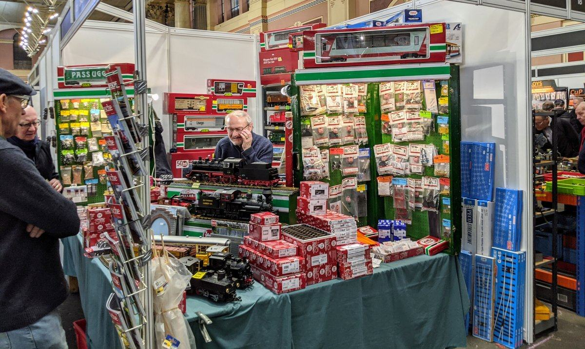 A stall holder at a model engineering exhibition is surrounded by model engines and accessories