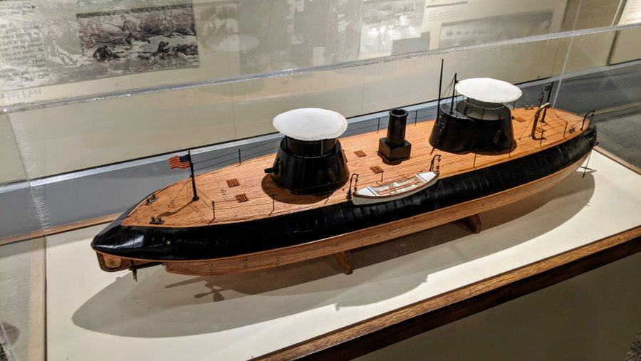 A model in a display case of an ironclad warship with two turrets