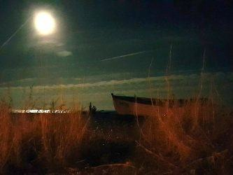 A bright moon illuminates a small fishing boat on a beach