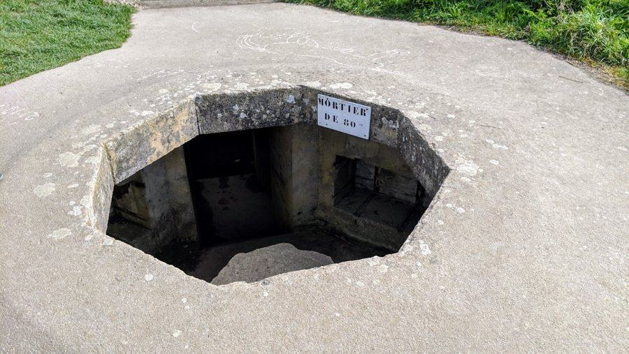Sunken concrete emplacement with a large hole in the top