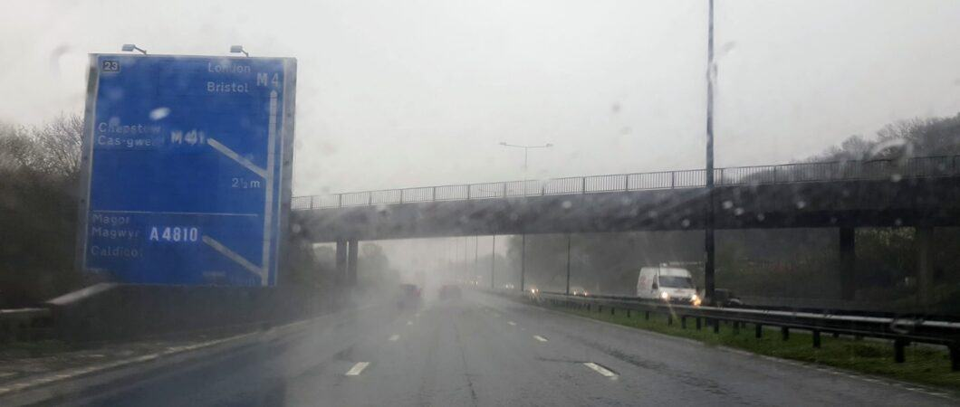 Looking through a car windscreen at rain and spray on the motorway