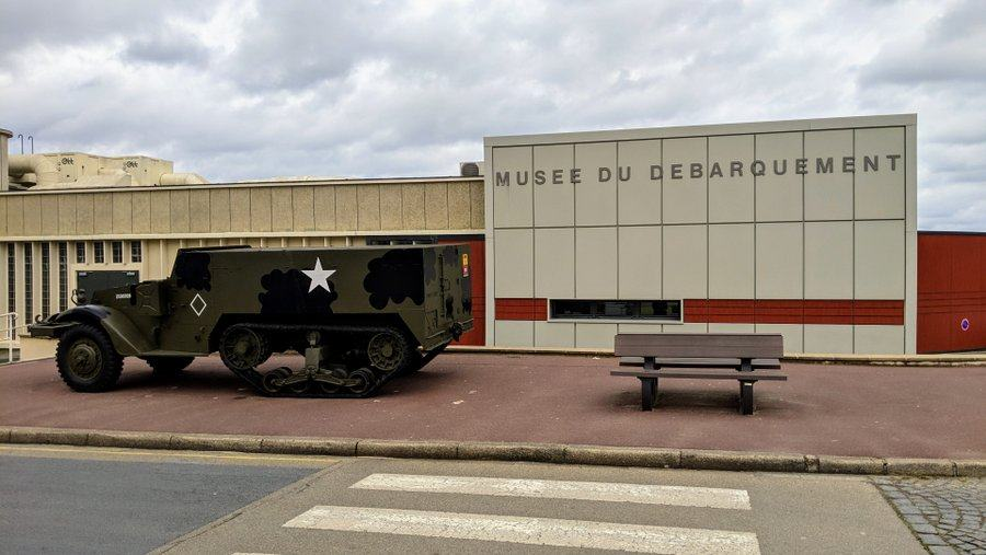 A camouflaged American half-track truck sits in from of the museum wall with the museum name on it