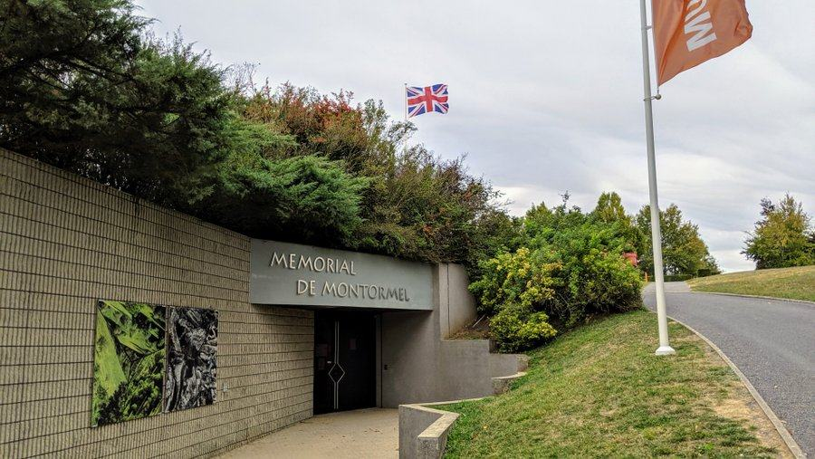 Modern entrance to a stone bunker with vegetation on the roof