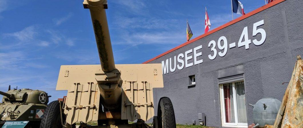 A 105mm howitzer stands guard outside the Musee 39-45 on a bright day