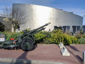 A green field gun sits in front of the curved silver wall of the Juno Beach Center, under a blue sky