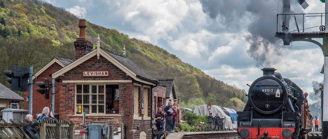 A steam train roars through a period railway station