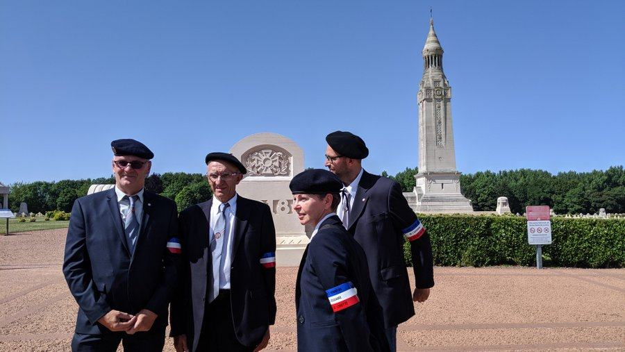 A group of men and one woman, all in black jackets & ties with berets on their heads and the French tricolour on their arms, stand in conversation in front of the graveyard