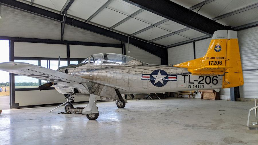 North American AT-28D Trojan in USAF colours, silver with a yellow tail, in a hanger at the Salis Flying Museum