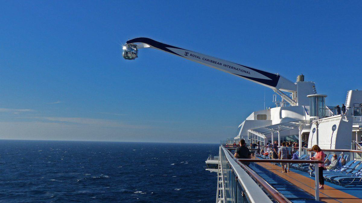 Ball-shaped passenger carying pod on the end of a crane arm dangles out to the side of a cruise ship over blue waters and against a blue sky.