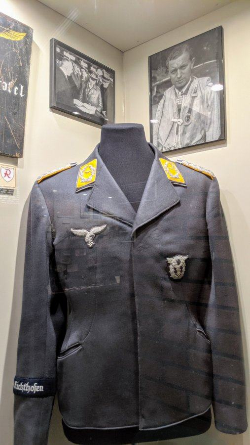 Luftwaffe ace, Walter Oesau's grey tunic with yellow epaulettes on display in a glass cabinet