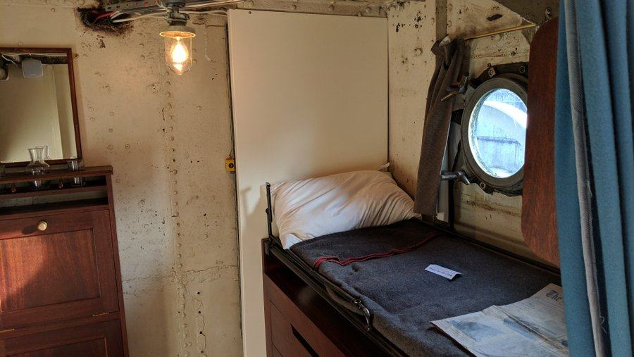 A tiny cabin with a bunk bed under a porthole