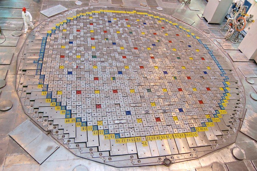 A worker in a white suit walks by a 60-ft circular steel grid of numbered and coloured small square access panels on the floor