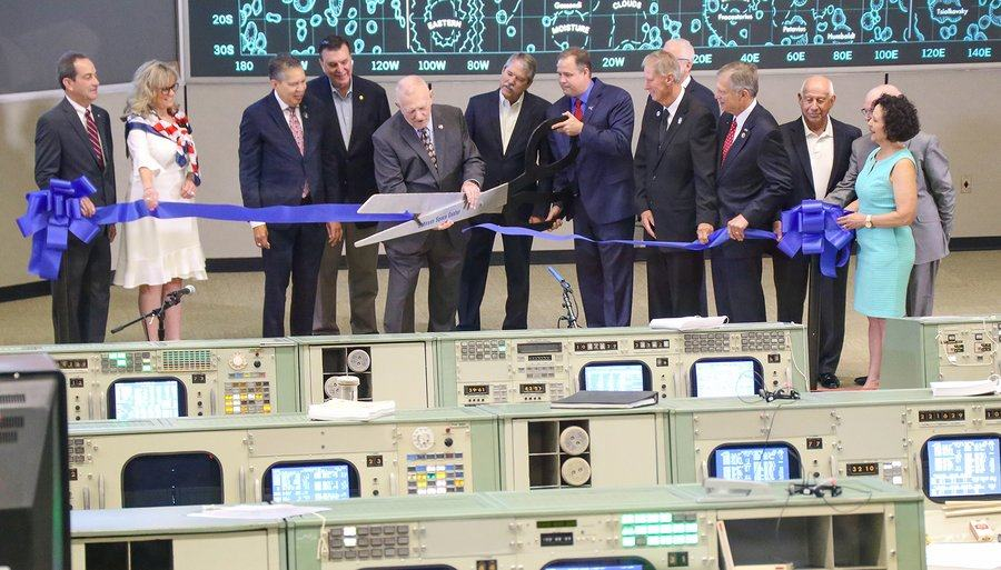 Ten VIPs on the floor of the NASA control room hold a large blue ribbon while former flight director, Gene Krantz cuts it with a giant pair of scissors