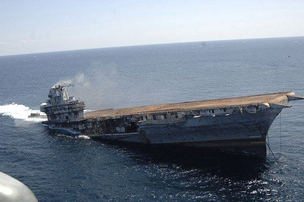 Aircraft carrier sinking by the stern, half submerged