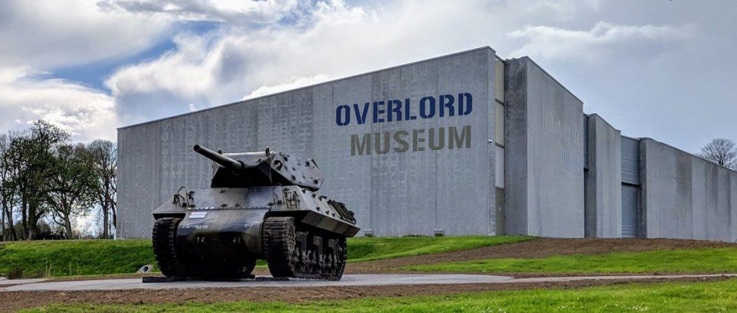 A dark green tank sits in front of a modern museum building