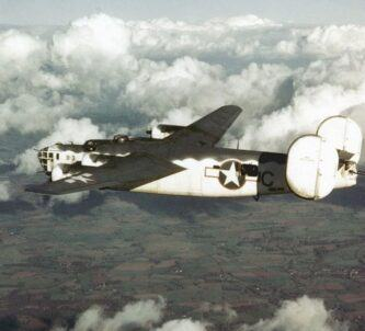 A US Navy four-engined bomber in white & grey flying over fields in England
