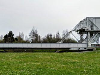 Grey-painted Pegasus bridge set in a grass park