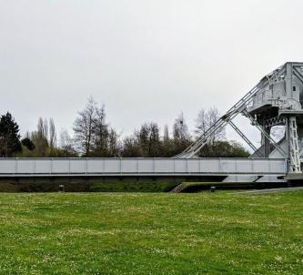 Grey-painted Pegasus bridge set in a grass park
