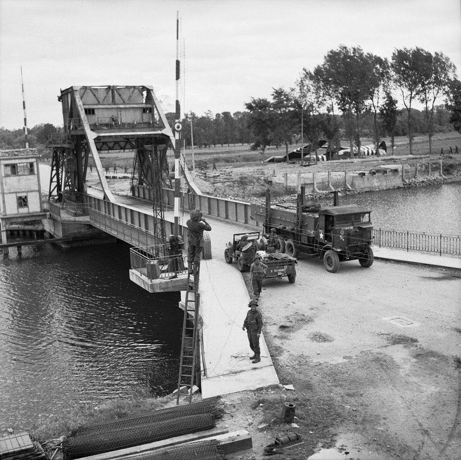 Black & white photo of pegasus bridge with Allied soldiers and vehicles on it
