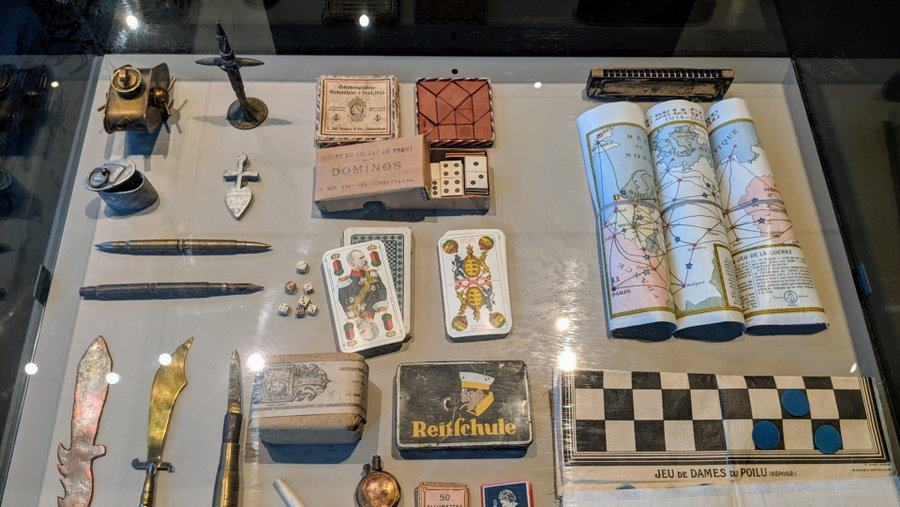A display case with playing cards , crucifixes, pens, a draughts board and a map