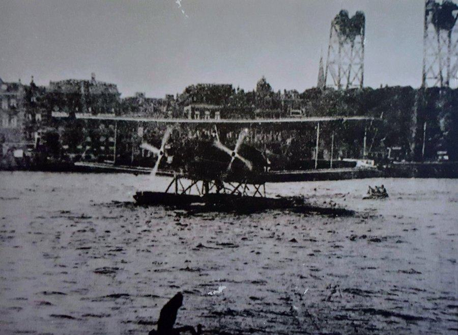 Old B/W photo of seaplane and rubber dinghy