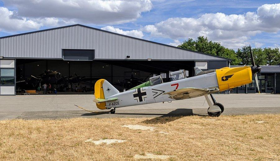 Small WW2 fighter in Luftwaffe colours on the apron in front of a hanger at the Salis Flying Museum