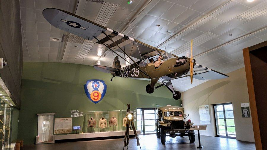 A small army light aircraft is suspended from the ceiling. On the floor is a military ambulance and there are display cases on the walls