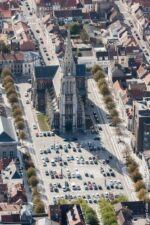 Aerial view looking down parked cars on the Place Crèvecœur which is dominated by the church of Saint Pierre