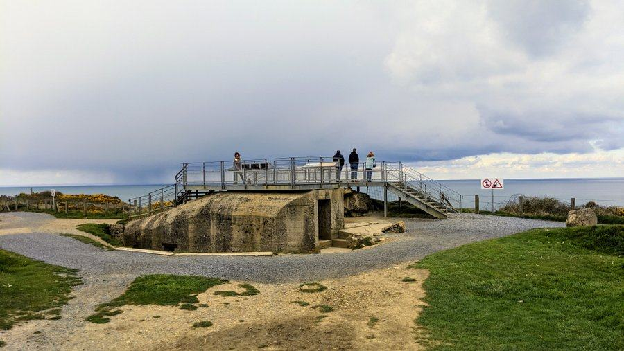 A concrete bunker with a modern steel viewing platform on top with visitors
