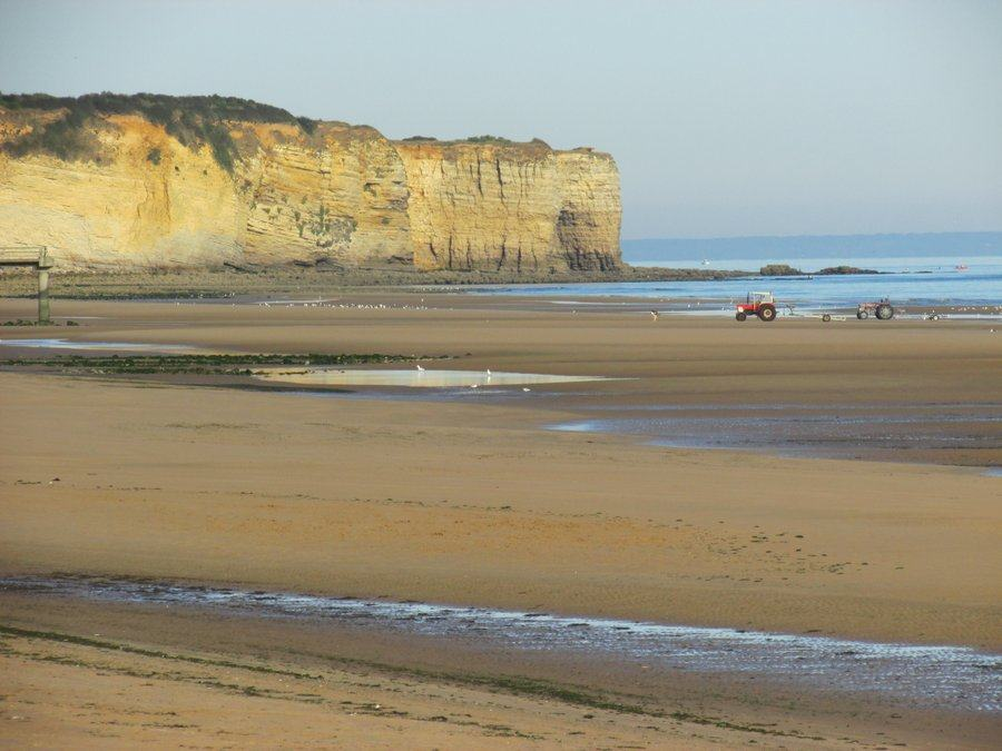 View at low tide across the beach to the cliffs of Point du Hoc in evening sunlight