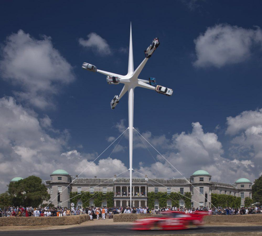 Six Porsche cars on spikes towering over Goodwood House on a sunny day