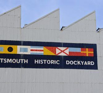 Colourful sign with signal flags on the side of a grey building