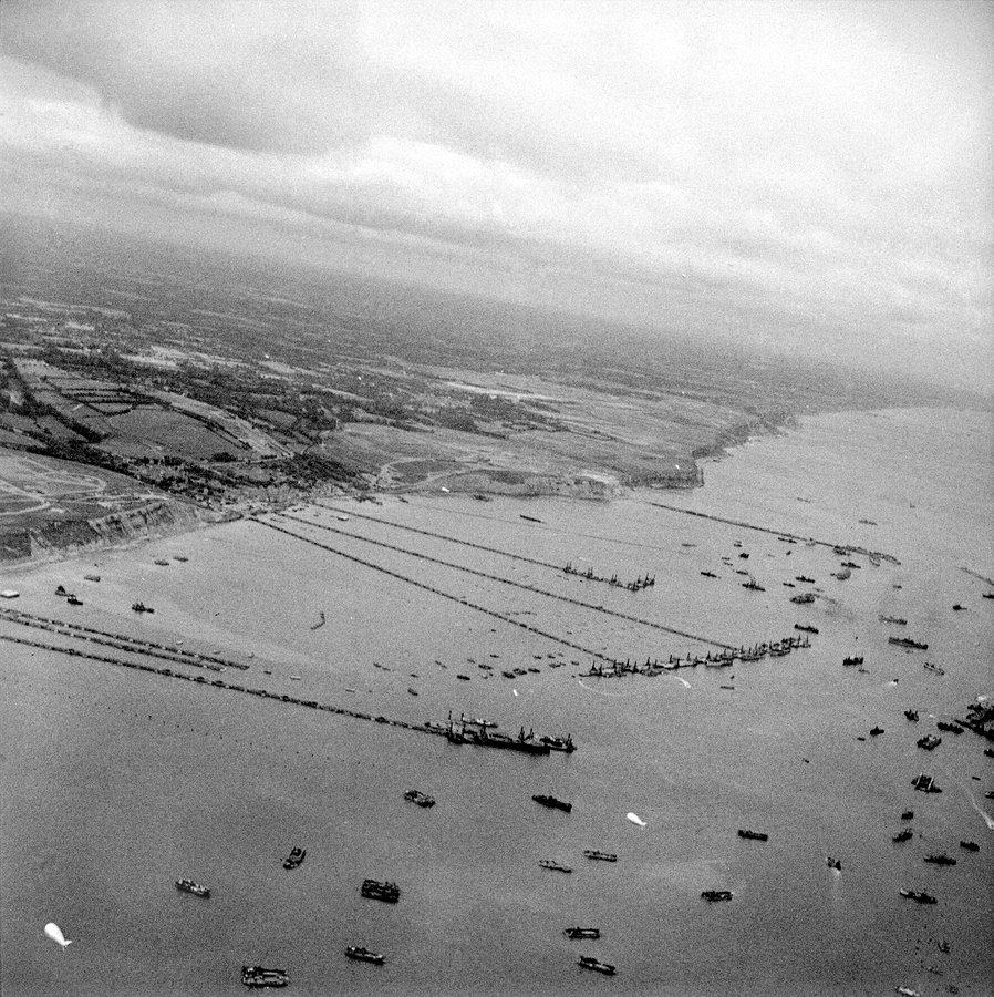 B&W aerial photo of the Mulberry harbour & shipping at Arromanches