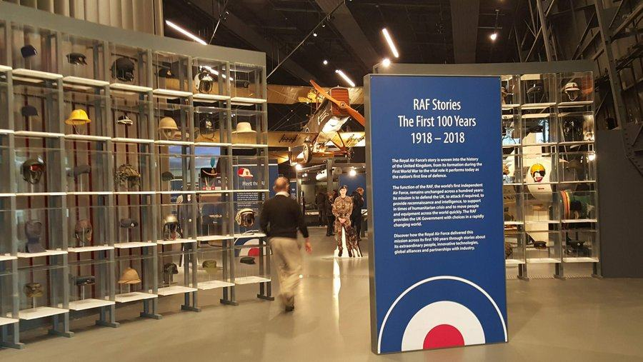 A welcome sign in the foreground and then perspex shelves with RAF headgear frame the entrance into the gallery