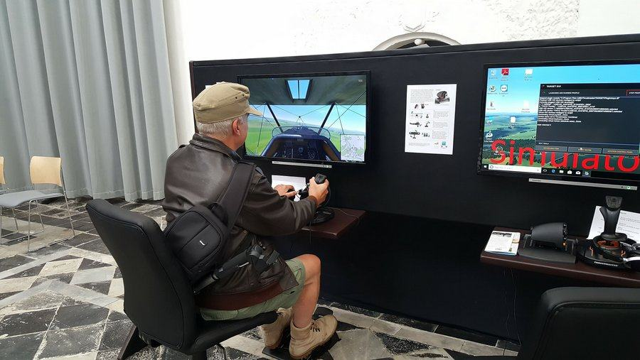 A man seated at one of the flight simulators in the 'St. Omer & the RAF' exhibition